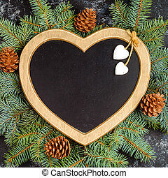 christmas or new year composition, heart shape frame and of christmas decoration and sparkles on black board background, flat lay. top view