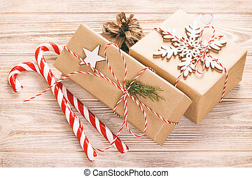 Christmas or New Year decorations background with pine cones, gift boxes and candy on white background. Toned