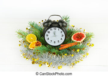 Christmas or New Year ornament. clock, spruce branches, spices, slices of oranges on a white wooden background.