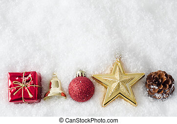 A row of Christmas ornaments, bordering bottom of frame, partially buried in white artificial snow. Copy space above.