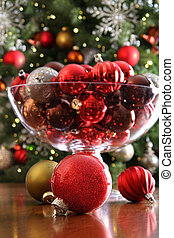 Christmas ornaments on table in front of tree