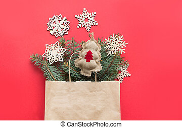 Christmas paper bag with gift and natural decor for Zero waste Holiday on red.