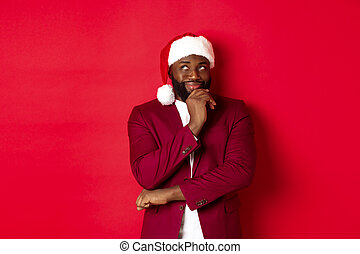 Christmas, party and holidays concept. Smiling african american man making new year plans, looking thoughtful at upper left corner, wearing santa hat, red background
