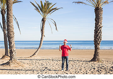 Christmas, people, holidays concept - Man in Santa hat showing thumbs up on the beach