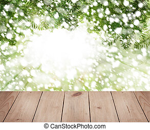 Christmas pine tree branch, snow and emty wooden board on abstract soft focus background
