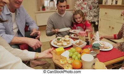 Family and friends gathered round a table at christmas time eating snacks whilst talking.