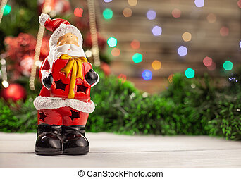 Christmas porcelain figure Santa Claus with a gift in hands on a white table against the background of a color garland