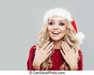 Christmas portrait of cheerful surprised woman in santa hat