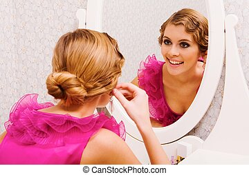 Image of pretty female looking in mirror and putting on earrings