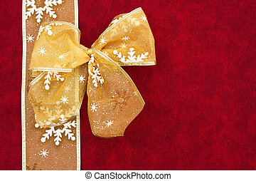 Christmas Present - A gold ribbon bow sitting with a...
