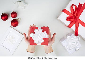 Christmas present on palms - Image of giftbox held by female...
