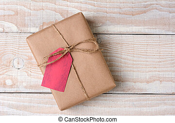 High angle shot of a plain brown paper wrapped Christmas present on a whitewashed wood table. The gift is tied with twine with a blank red gift tag.