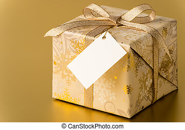Christmas present with gold ribbon and blank tag