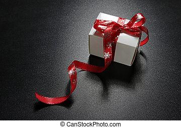 christmas present with red ribbon on black background