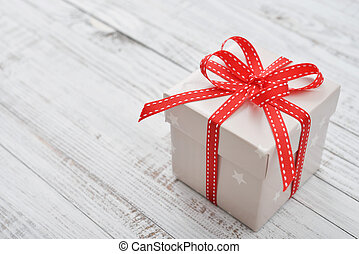 Christmas present wrapped in decorative wrapping paper with red ribbon closeup