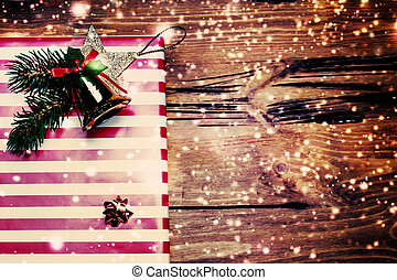Christmas Present wrapped in red paper on a wooden background with falling winter snowflakes and copyspace for your greeting text