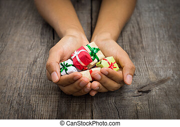 A person holding Miniature christmas presents on wood background.