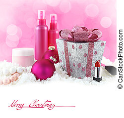 Christmas presents, beauty products with snow and pink background