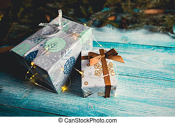 Christmas presents on blue wooden table with fir sprigs