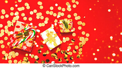 Christmas presents on red background with sparkles. Close-up, copy space