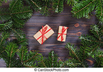Christmas presents with red ribbon on dark wooden background in a frame made of fir branches with canes. Flat lay style