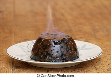 Christmas pudding on fire on a wooden table
