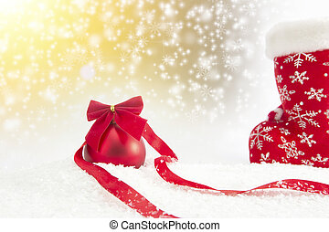 Christmas red ball with ribbon on snow