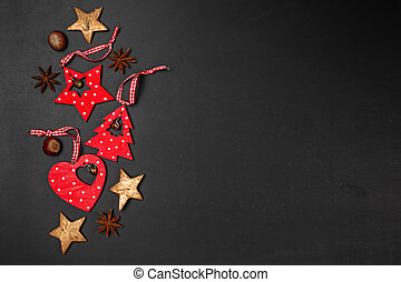 Christmas red wooden ornaments with nuts and star anise on black background, top view, flat lay