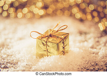 Christmas retro gold box in the snow with golden background light