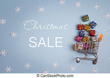 Christmas sale and shopping trolley with gift boxes.