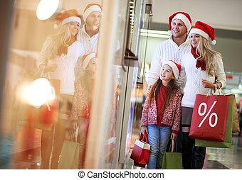 Christmas sale - Portrait of happy family in Santa caps...