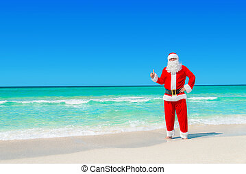 Christmas Santa Claus at tropical beach thumbs up hand gesture