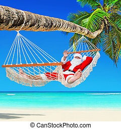 Christmas Santa Claus relax in hammock at tropical palm beach