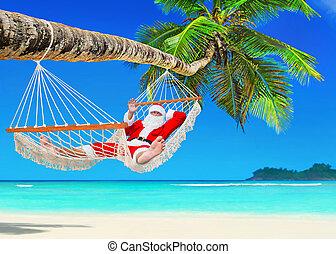 Christmas Santa Claus relaxing in hammock at tropical palm beach