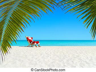Christmas Santa Claus relaxing on sunlounger at ocean sandy tropical palm beach