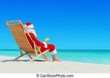 Christmas Santa Claus with fresh juice on sunlounger at...