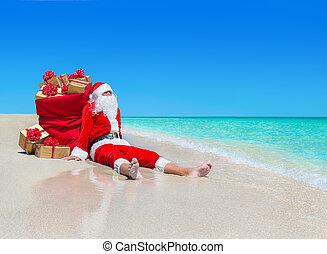 Christmas Santa Claus with gift boxes sack at tropical beach...