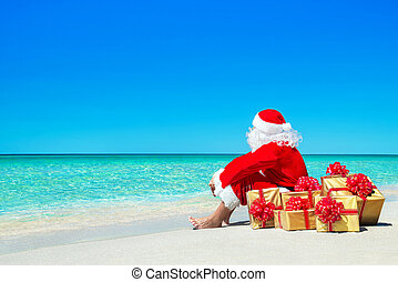 Christmas Santa Claus with gift boxes relaxing at ocean...