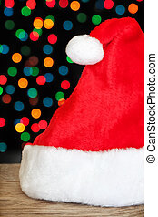 Christmas santa hat on a background of colored bokeh.