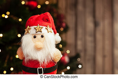Christmas Santa toy on the background of a Christmas tree with garlands on a wooden background