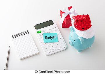 Piggy bank wearing christmas hat with word budget on calculator and notepad with pen, christmas saving and budget concept