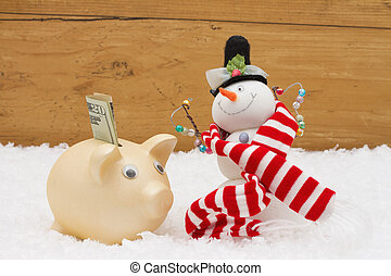 Christmas Savings, Piggy Bank and Snowman with scarf on snow with copy-space