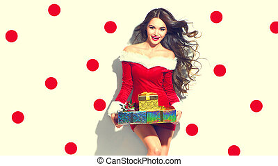 Christmas scene. Sexy Santa. Beauty model girl wearing red party costume holding gifts