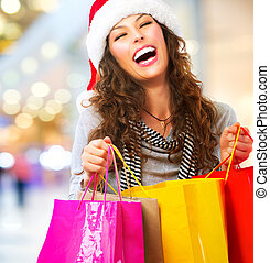 Christmas Shopping. Woman with Bags in Shopping Mall. Sales