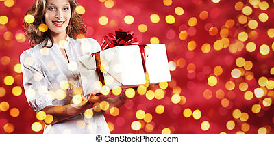 christmas shopping, woman with gift package on blurred bright li