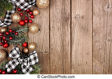 Christmas side border with white and black checked buffalo plaid ribbon, decorations and branches, overhead on a rustic wood background