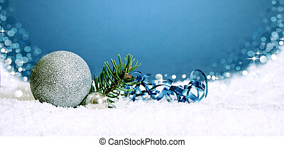 Christmas silver bauble and snow isolated on blue .