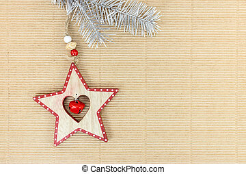 christmas silver firtree branch with wooden star on corrugated brown cardboard