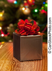 Christmas. Silver gift box with red ribbon on festive background
