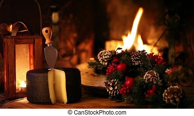 Video clip of nice Christmas scene in front of the fireplace, showing typical Italian seasoned cheese and Christmas decorations.
